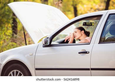 A young woman waits for assistance in her car