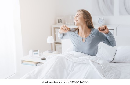 Young woman waking up in her bed and stretching, she is starting a new day with energy and vitality