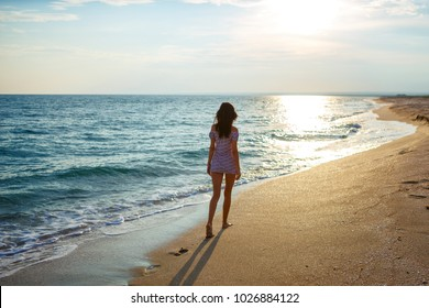 Young woman walk on an empty wild beach towards celestial beams of light falling from the sky, the concept of travel and tourism, leisure at sea