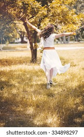 Young woman walk in park, wear white dress. Autumn. Vintage toned photo.