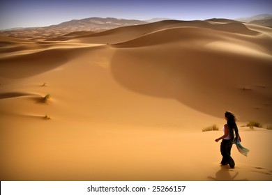 Young woman walking alone in the desert. Moroccan background