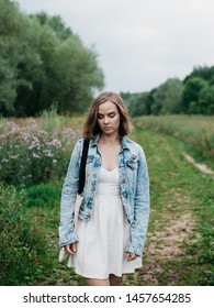 Young woman walking alone in field during summer overcast evening