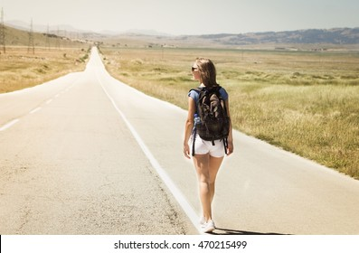 Young woman walking alone on a long road
