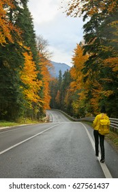 Young woman walking along asphalt road in colorful autumn forest against mountains.