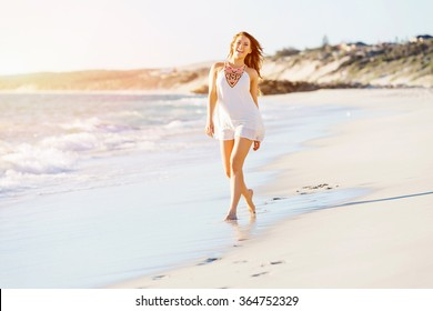 Young woman walking along the beach