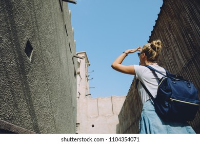 Young woman walking along narrow street of Dubai with old buildings, UAE