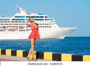 Young woman walking along the quay, the ship sailing by