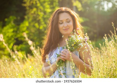 Young woman walking among wildflowers on sunny summer day. Concept of the joy of communicating with summer nature