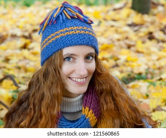 Young woman is walking in the autumn wood among yellow maples