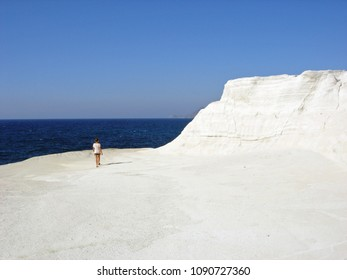 Young woman walking away on a white cliff by the sea in Milos, Greece