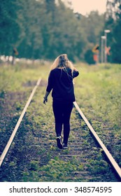 A young woman is walking away on a railroad track. She is wearing black clothes and has a long hair. Tracks are abandoned. Image has a vintage effect applied.