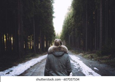 Young woman walking away on a forest path.