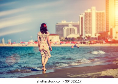 Young woman walking back to camera at sunset on the beach in Tel Aviv, Israel