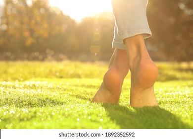 Young woman walking barefoot on fresh green grass, closeup