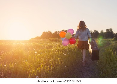 Young Woman walking with big suitcase and colored balloons on meadow road. Sunrise, wild flowers, summer  freedom and travel