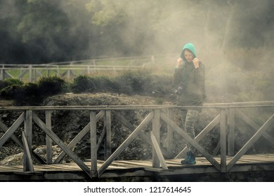 Young woman is walking by the trail near by volcano. She is observing it. You can see fog around her. Azores islands, Sao Miguel, Portugal. Furnas lake.