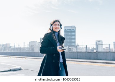 young woman walking in the city back light listening music headphones with smart phone hand hold - music, relaxing, enjoyment concept