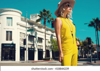 Young woman walking in a city in yellow jumpsuit, nude hat, necklace, black handbag. Fashion summer photo. Bright colors