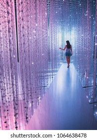 Young woman walking down the light corridor made of diamonds with several colours.