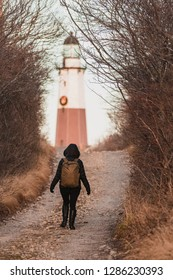 Young woman walking down a pathway leading towards a lighthouse, framed by woodland trees.
