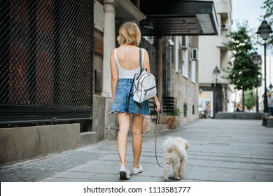 Young woman walking down the street with her pet dog
