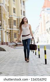 Young Woman Walking Down the Urban Street