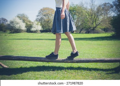 A young woman is walking in the forest and is balancing on a wooden beam