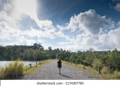 Young woman walking the forest road with beautiful view on the lake in the Khao Yai National park with blue and cloudy sky.