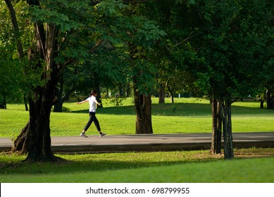 A young woman is walking for health in the park, public park in the morning