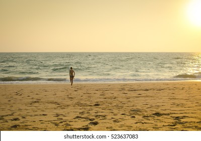 Young woman walking into the sea
