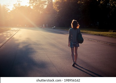 A young woman is walking into the sunset in a park