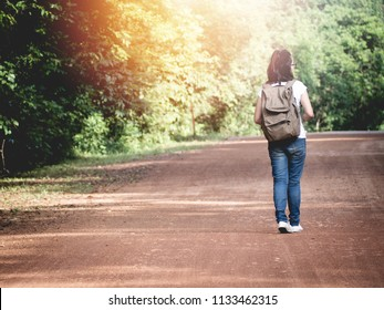 young woman walking into woods, wild adventure.