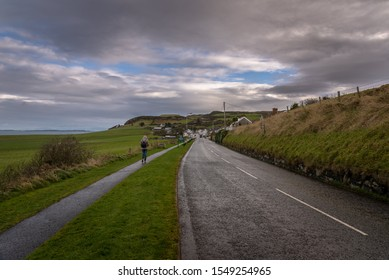 Young woman walking lonely along a road towards to a coastal city on a cold and rainy day with fields and the sea aside while grass is blown by the wind. Concept of being lonely and sadness.