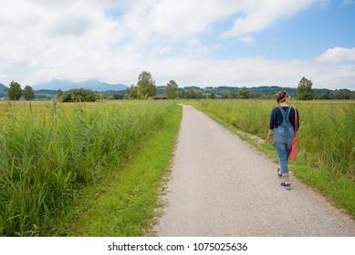 young woman walking at loop road around natural site chiemsee, idyllic bavarian landscape