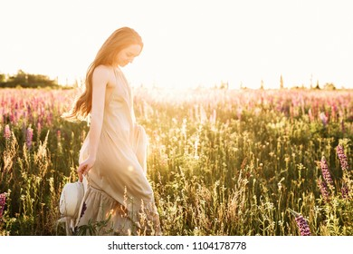 Young woman walking in lupine flower field with sunrise on the background. Warm orange sunbeam light