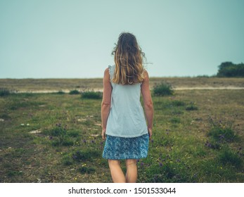 A young woman is walking in a meadow on a foggy day