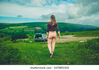 A young woman is walking in nature after parking her car