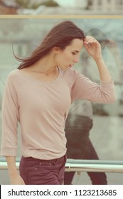 A young woman walking near a glass wall in the city. Street dress style. She wears Burgundy jeans, a pink shirt. Fashionable pose