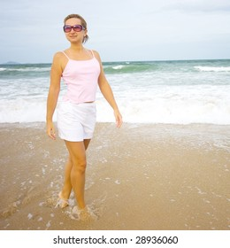 Young woman walking near ocean in sunglasses