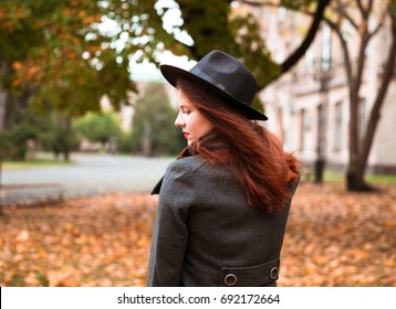 Young woman walking on autumn city park. Beautiful fall time in nature