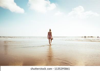 Young woman walking on beach shore