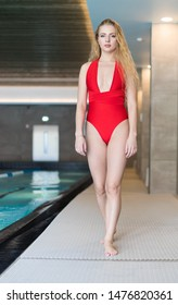 Young woman walking on the boarder of a swimming pool in a spa