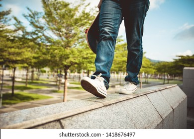 Young woman walking on the edge of a urban building wall at city