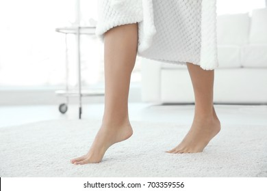 Young woman walking on floor after shower