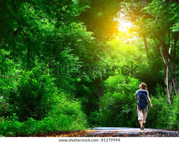 森の緑のアスファルト道を歩く若い女性