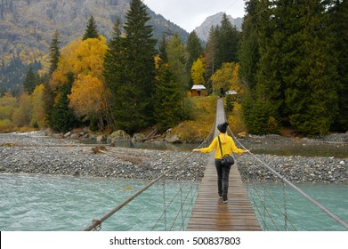 Young woman walking on hanging bridge over river against autumn forest.
