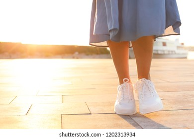 Young woman walking on pier at sunset light. Space for text