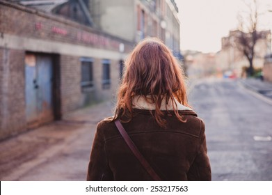 A young woman is walking on the quiet streets of a city in the winter
