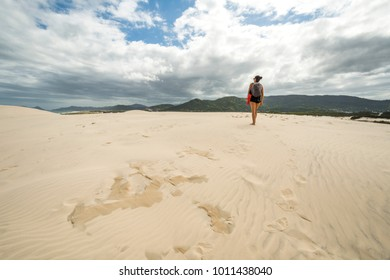 Young woman walking on sand dunes in Joaquina Beach, Florianopolis, Santa Catarina Island, South Brazil