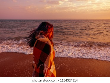 Young woman walking on sand coast near the sea at sunset.